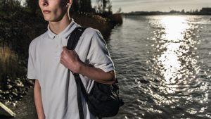 Jongen met rugzak langs het water