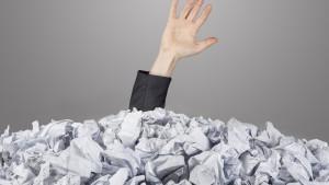 Hand steekt uit berg gekreukt papier