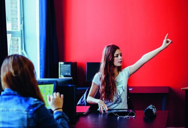 Een leerling steekt haar hand op in de computerklas