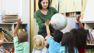 Leraar toont wereldbol aan multiculturele klas