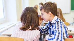 Twee vrienden fluisteren met elkaar in de klas