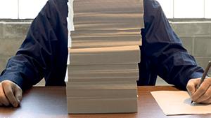 Leraar achter stapel papierwerk