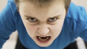 Jongen kijkt boos en met ontblote tanden in de camera
