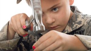 stoer meisje met gelakte nagels klopt met hamer op spijker