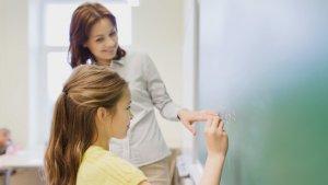 meisje aan het schoolbord met haar juf