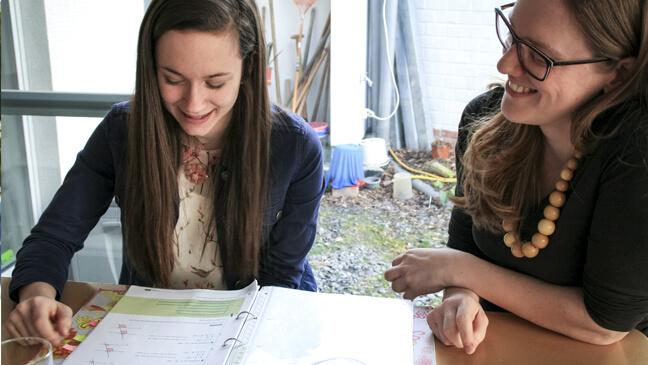 Elise zit achter een cursusmap met haar GON-begeleidster