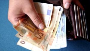 close up van hand die geld uit een portefeuille haalt