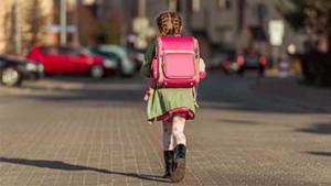 Meisje met rugzak wandelt door stad naar school