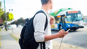 Jongen met rugzak staat te wachten op bus