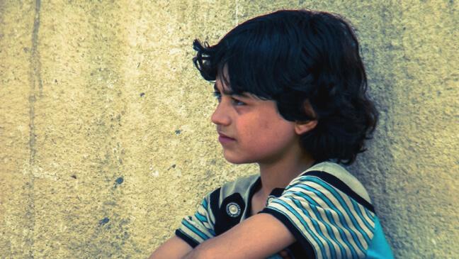Syrische jongen leunt tegen muur