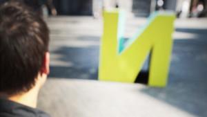 Jongen kijkt naar sculptuur van de letter 'N'