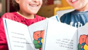 Kinderen tonen boekjes met Nederlandse en Arabische tekst