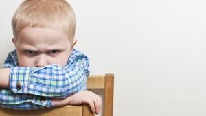 Kind met gekruiste armen kijkt boos in de lens