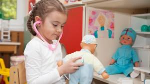 Meisje speelt dokter met poppen