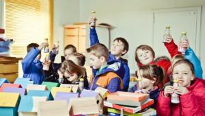 kinderen vullen flesjes met gekleurd zand