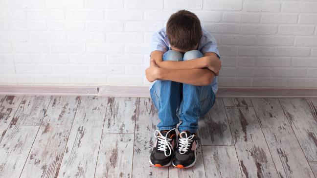 jongen zit in elkaar gedoken tegen een muur