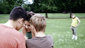 groepje jongens praat over meisje in de achtergrond