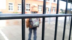 kind op speelplaats, gezien door de schoolpoort