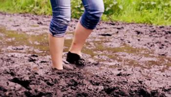 Meisje wandelt door de modder met opgestroopte broek (Blotevoetenpad)