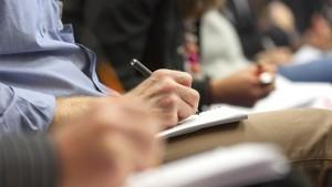 close up van mensen die noteren tijdens een lezing