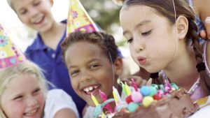 Meisje blaast kaaren uit tijdens verjaardagsfeest