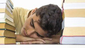 Moslimjongen slaapt tussen boeken