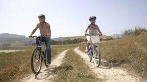 Vader en dochter fietsen door weilanden