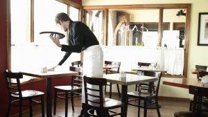Kelner veegt tafel af in café