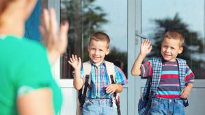 mama wuift kinderen uit aan schoolpoort