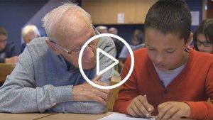 Oudere man en kind maken samen een oefening in de klas