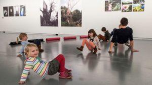 Een groep je kinderen lopen op handen en voeten door het Fotomuseum