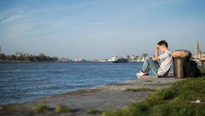 Jongen met rugzak zit langs het water
