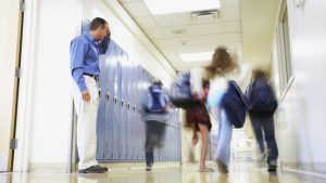 Leraar kijkt naar leerlingen die in de hal lopen