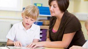 Leerkracht helpt meisje bij lezen