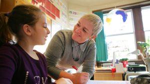 leerkrachte helpt leerling
