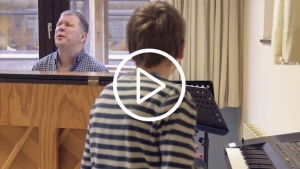 blinde leraar Geert achter de piano