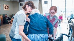 2 vrouwen helpen oudere in zorgcentrum