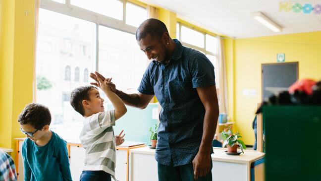 Leraar Mathew geeft high five aan leerling